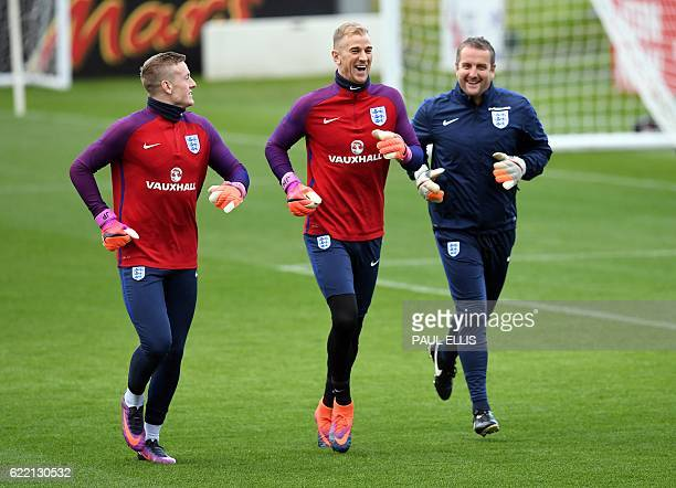 England goalkeepers Jordan Pickford and Joe Hart reacts as they run with goalkeeping coach Martyn Margetson during a team training session at St...