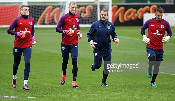 England goalkeepers Jordan Pickford Joe Hart and England's goalkeeper Tom Heaton react as they run with goalkeeping coach Martyn Margetson during a...