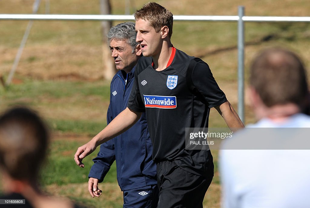 England goalkeeping football coach Franco Tancredi (L) walks with replacement defender Michael Dawson as he arrives for a training session at the Royal Bafokeng Sports Campus near Rustenburg on June 5, 2010. Dawson was flown from England to replace captain Rio Ferdinand after he injured his knee during the team's first training session in the country prior to the World Cup 2010 kick-off in South Africa.