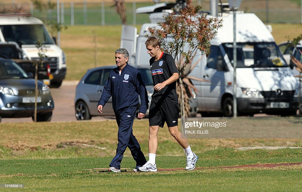 England goalkeeping football coach Franco Tancredi walks with replacement defender Michael Dawson as he arrives for a training session at the Royal Bafokeng Sports Campus near Rustenburg on June 5, 2010. Dawson was flown from England to replace captain Rio Ferdinand after he injured his knee during the team's first training session in the country prior to the World Cup 2010 kick-off in South Africa.