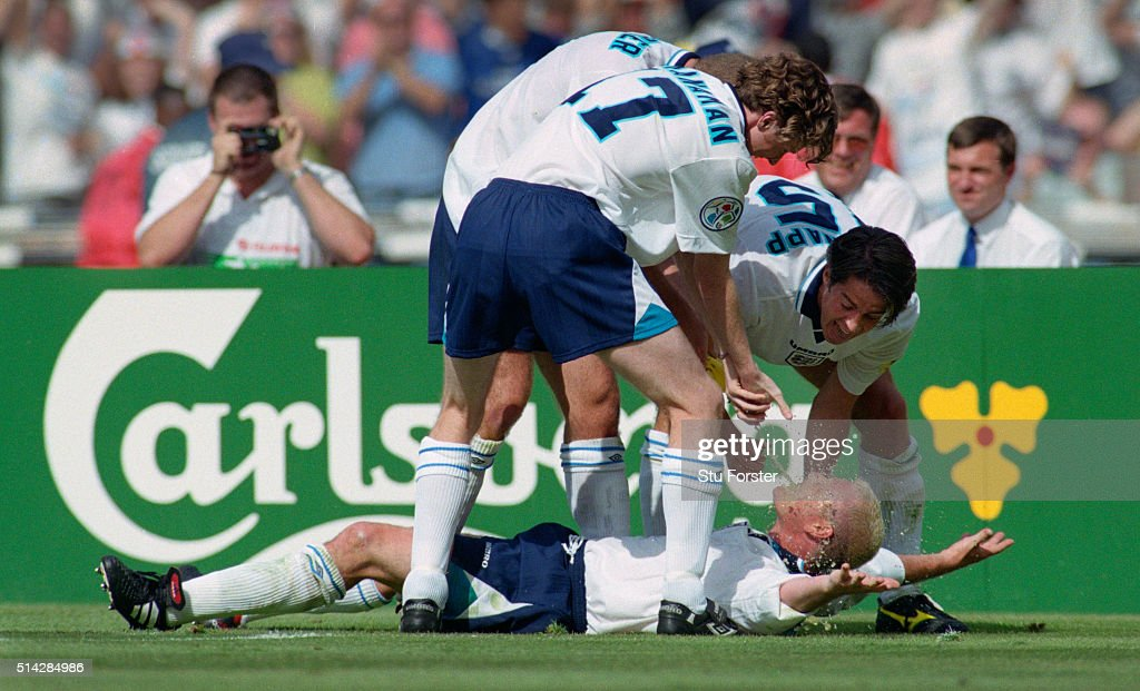 England goalscorer Paul Gascoigne celebrates in the 'Dentists Chair' with Steve McManaman (l) Teddy Sherringham (obscured) and Jamie Redknapp during the 1996 European Championships group stage match against Scotland at Wembley Stadium on June 15, 1996 in London, England.
