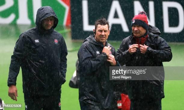 England head coach Eddie Jones looks on with Scott Wisemantel the England attack coach and forwards coach Steve Borthwick during torrential rain...