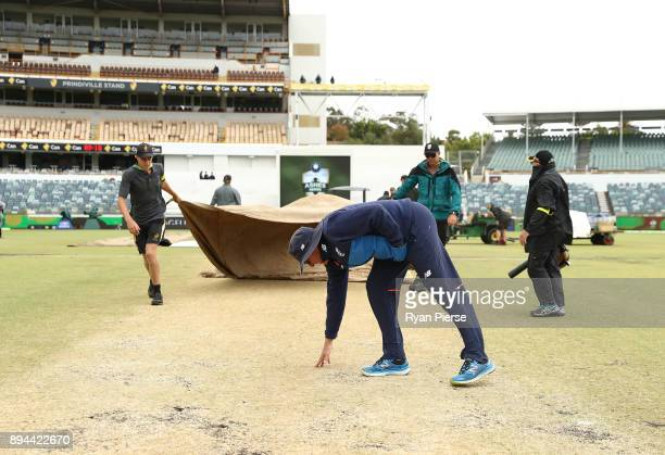 England Head Coach Trevor Bayliss inspects the wet pitch as rain delays the start of play during day five of the Third Test match during the 2017/18...