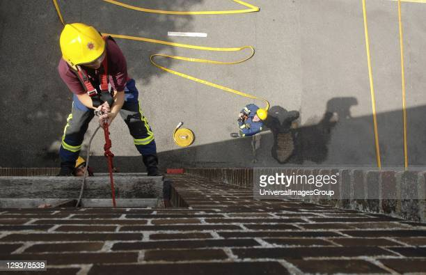 England Hertfordshire Firefighter climbing rope up side of building during training exercise A firefighter climbing a rope up the side of a building...