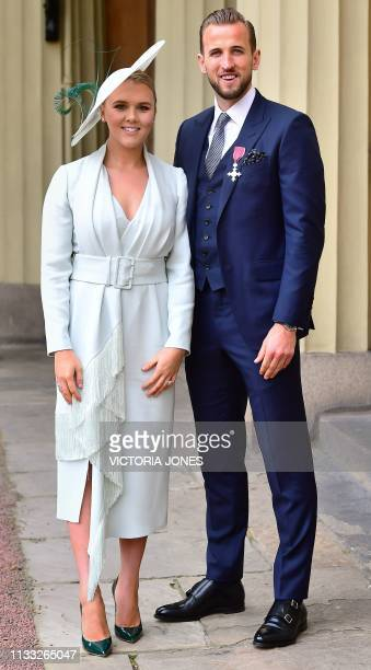 England international football captain Harry Kane wears his medal as he poses with his partner Kate Goodland after being appointed Member of the...