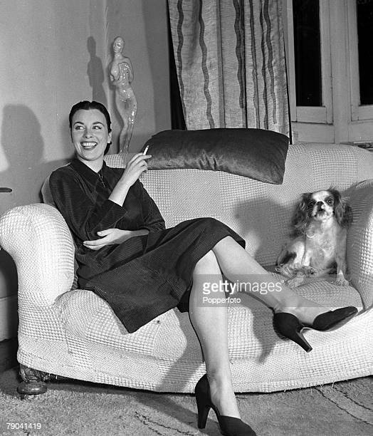 England Irish born actress Constance Smith is pictured with her dog as she smokes a cigarette