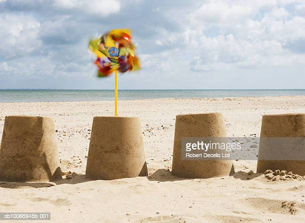 England, Isle of Wight, row of sandcastles on beach, one with windmill, blurred motion