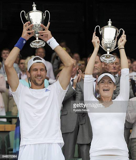 England - Jurgen Melzer from Australia and Iveta Benesova of Czech Republic hold their trophies high at the awards ceremony after winning the mixed...