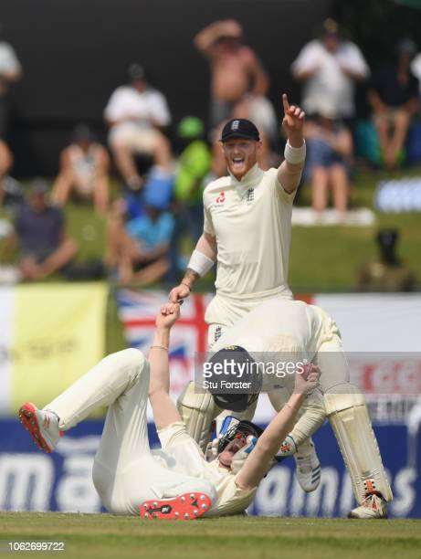 England keeper Ben Foakes and Ben Stokes congratulate catcher Keaton Jennings after he had caught Sri Lanka batsman Dhananjaya de Silva during Day...