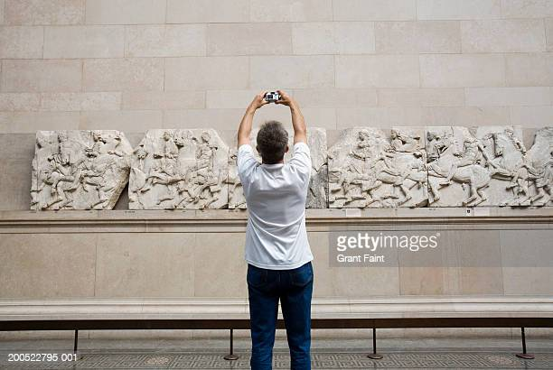 england, london, british museum, mature man taking photo of carving - british museum stock pictures, royalty-free photos & images