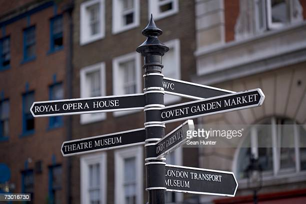 england, london, covent garden,  black and white signpost with directions to covent garden market, the royal opera house and various museums. - covent garden - fotografias e filmes do acervo