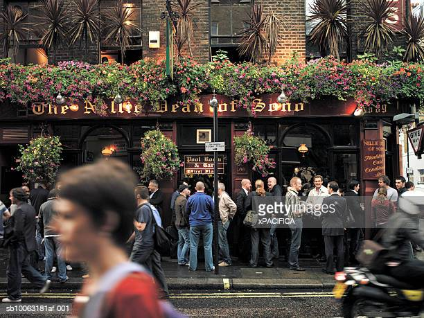 england, london, crowds in front of pub, pedestrian in foreground, blurred motion - british culture stock pictures, royalty-free photos & images