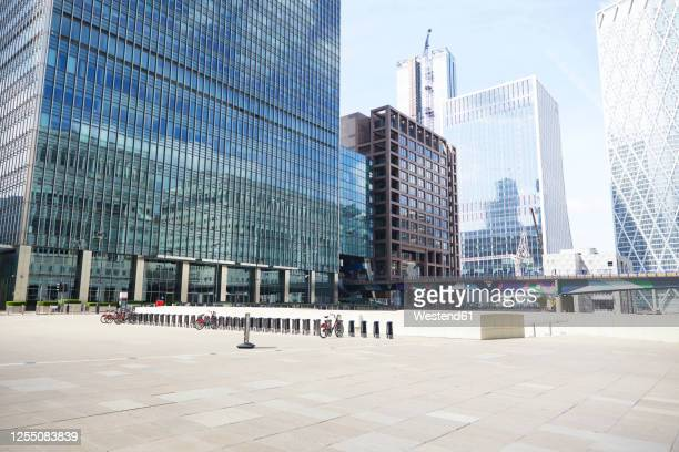 uk, england, london, empty square inlondon docklands withskyscrapers in background - city stock pictures, royalty-free photos & images