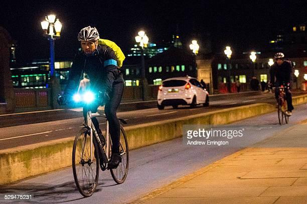 England London Southwark Bridge man riding bicycle at night Blurred motion