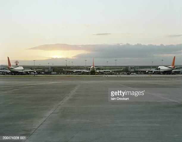 England, London, three planes waiting at Heathrow airport, dusk