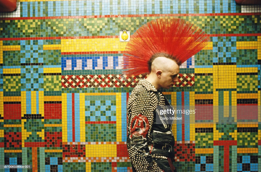 Punk with mohawk in front of mosaic : News Photo