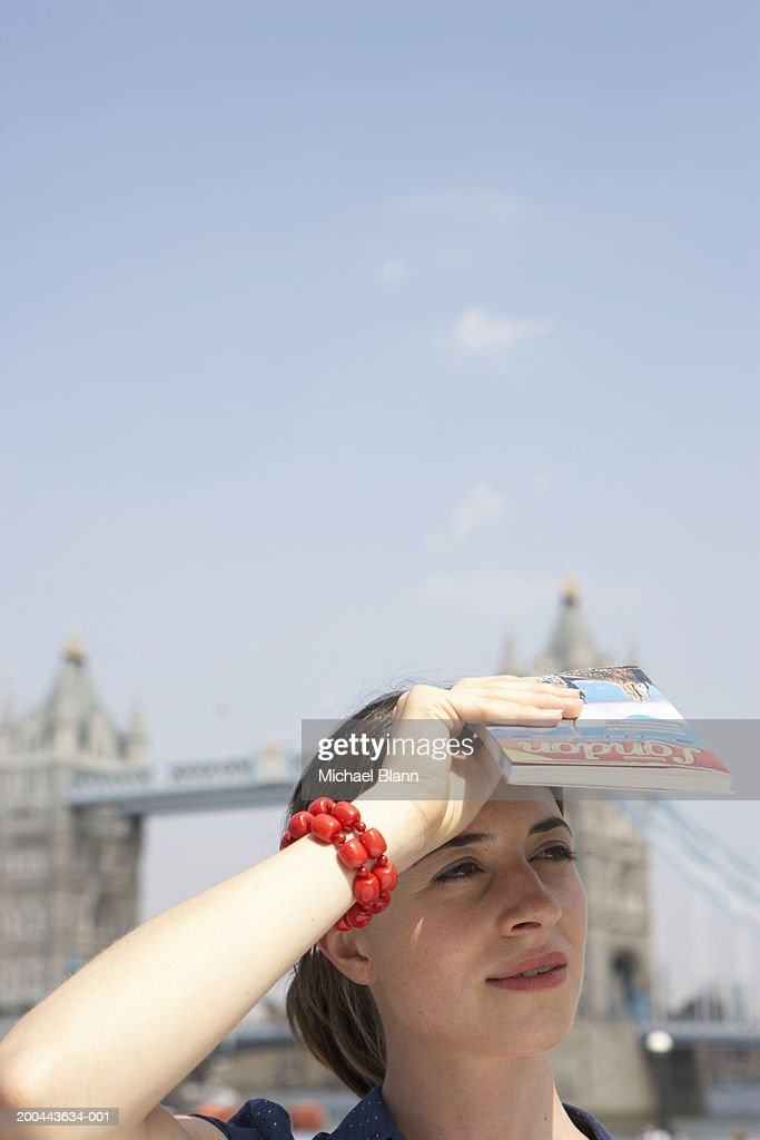 England, London, woman shielding eyes from sun, close-up : Stock Photo