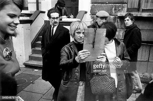 England London young girl on street market looking into mirror Portobello Road