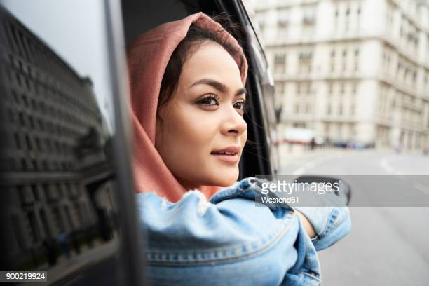 UK, England, London, young woman wearing hijab looking out of a taxi