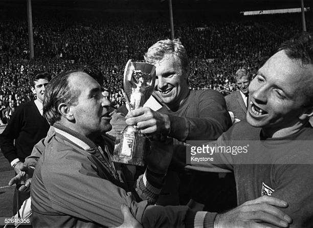 England Manager Alf Ramsey celebrates his team's 42 victory in extra time over West Germany in the World Cup Final at Wembley Stadium With him is...