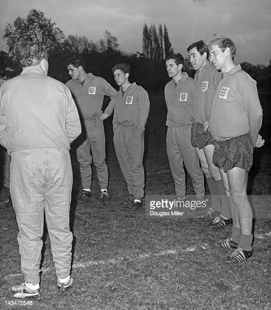 England manager Alf Ramsey talks to players during a training session at Roehampton London 7th December 1964 The four players on the right are Alan...