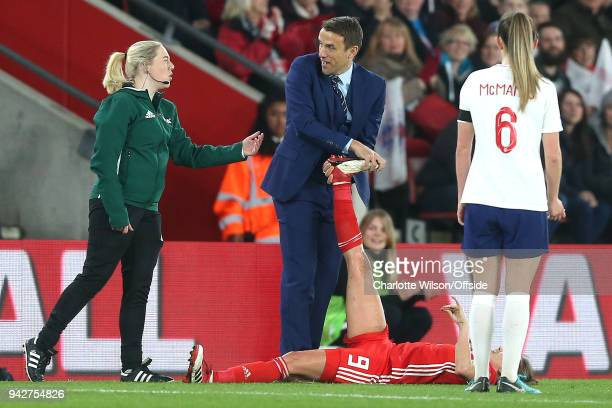 England manager Phil Neville expresses disbelief as he is asked to stop stretching out the leg of Kayleigh Green of Wales by a FIFA official during...