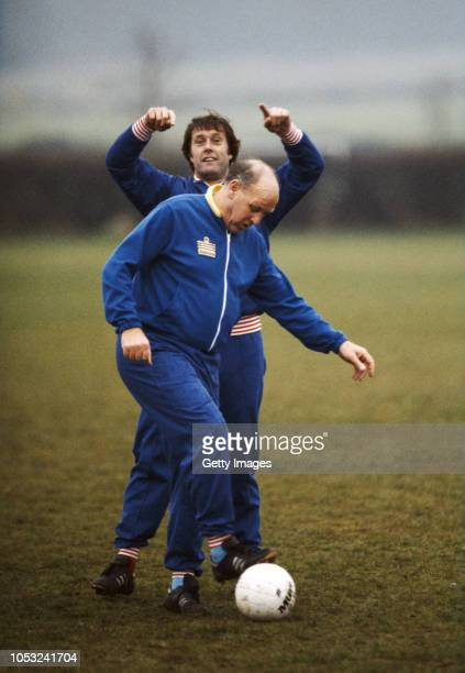 England manager Ron Greenwood and coach Geoff Hurst wearing Admiral Tracksuits, share a joke during an England training session circa 1981 in England.