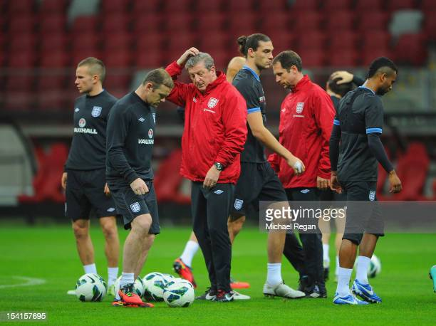 England manager Roy Hodgson scratches his head as Wayne Rooney Andy Carroll and Ashley Cole look on during the England training session ahead of...