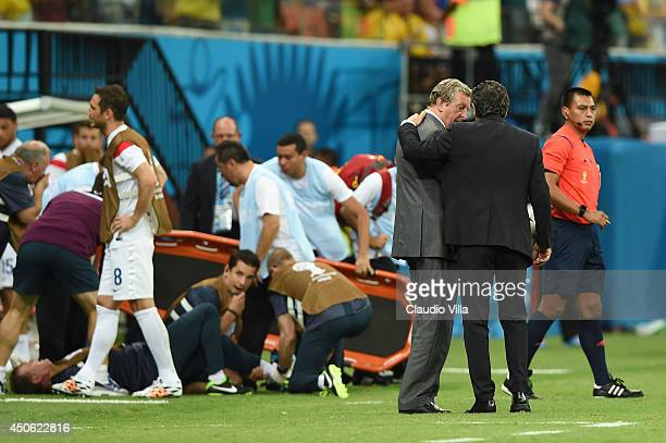 England manager Roy Hodgson speaks to head coach Cesare Prandelli of Italy as England trainer Gary Lewin lies on the ground being treated for an...