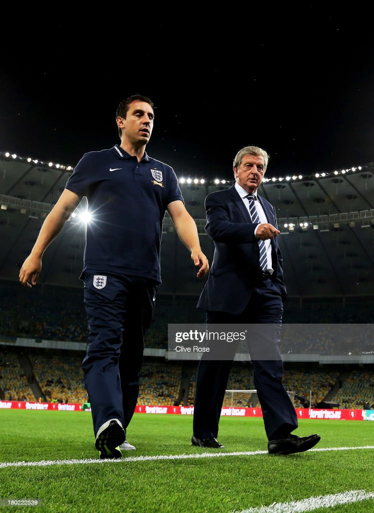England manager Roy Hodgson (R) speaks with his assistant coach Gary Neville (L) prior to kickoff during the FIFA 2014 World Cup Qualifying Group H match between Ukraine and England at the Olympic Stadium on September 10, 2013 in Kiev, Ukraine.