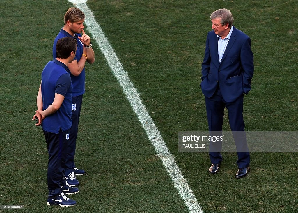England manager Roy Hodgson (R) talks to England goalkeeping coach Dave Watson and England coach Gary Neville in the stadium in Nice, France on June 26, 2016 during the Euro 2016 football tournament. / AFP / PAUL