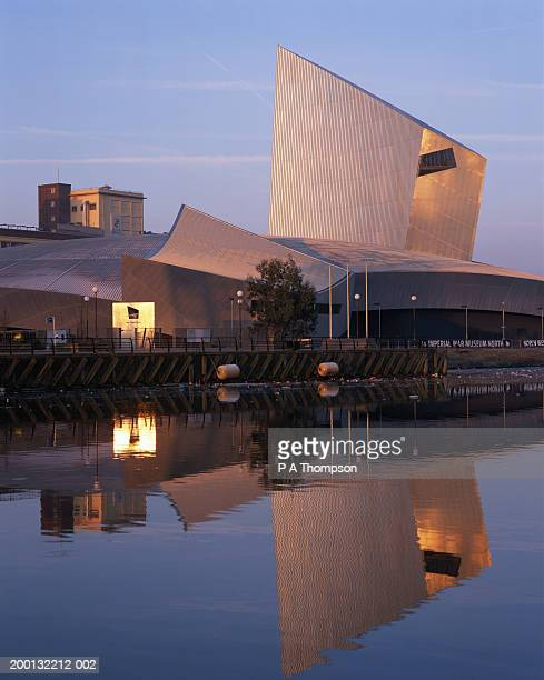 england, manchester, salford quays, buildings reflected in water, dawn - imperial war museum museum stockfoto's en -beelden