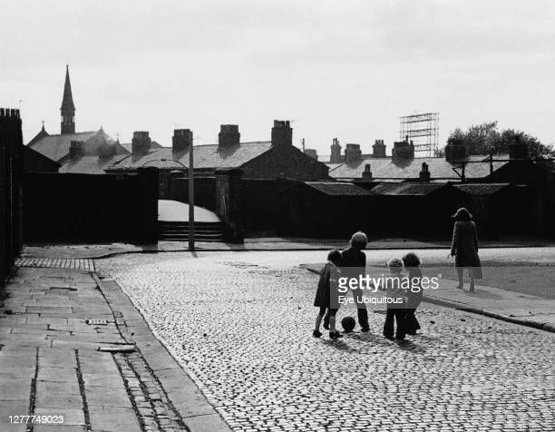 England, Merseyside, Kirkdale, Children playing soccer on cobbled street, 1972.