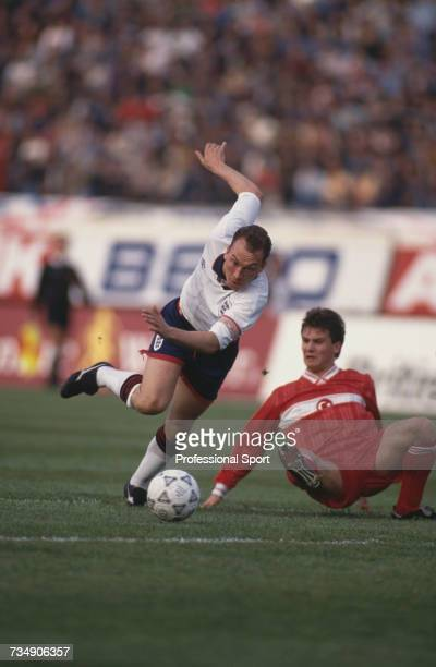 England midfielder and captain of the national team, David Platt trips as he is tackled by a Turkish player during play in the FIFA World Cup Group 2...