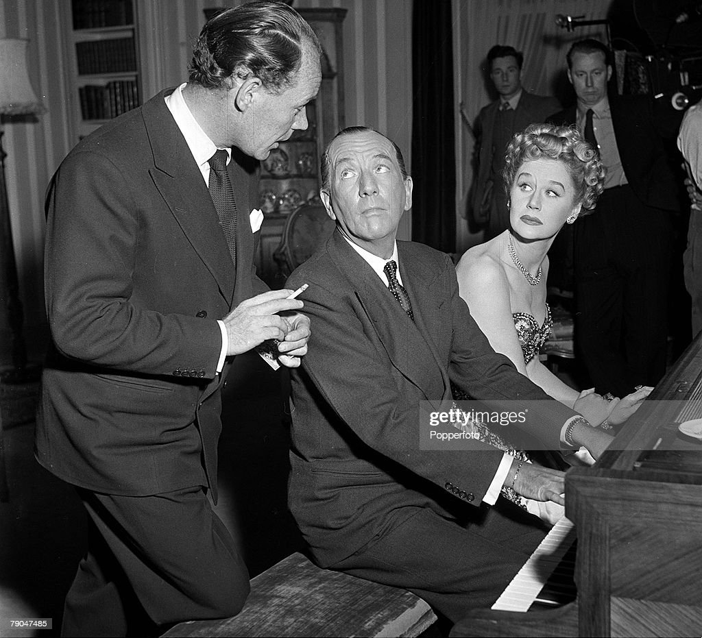 1949. Inglaterra.  Molyneux diseña ropa para Margaret Leighton para la película 'The Astonished Heart'.  En la imagen, en el plató, están el dramaturgo inglés, el actor y compositor Noel Coward, tocando el piano, flanqueado por el codirector Antony Darnborough (izquierda) y Mar: Fotografía de noticias
