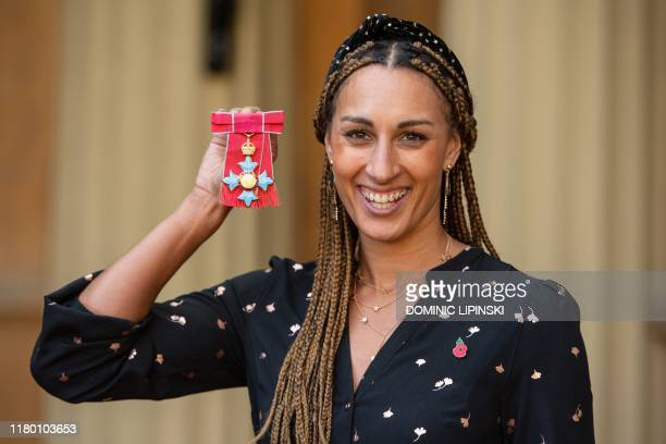England netball player Geva Mentor poses with her medal after being appointed a Commander of the Order of the British Empire during an investiture...