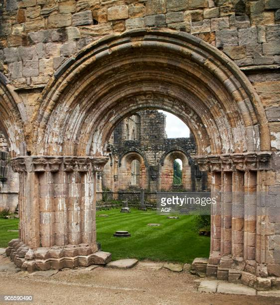England NorthYorkshire Romanesque arch North Yorkshire the ruins of the 12th century Cistercian Abbey known as Fountains Abbey one of the finest...