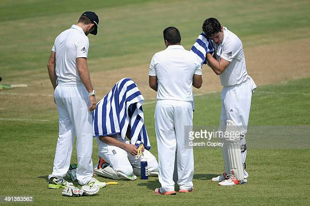England opening batsmen Moeen Ali and captain Alastair Cook try to cool down during a drinks break during day one of the tour match between Pakistan...