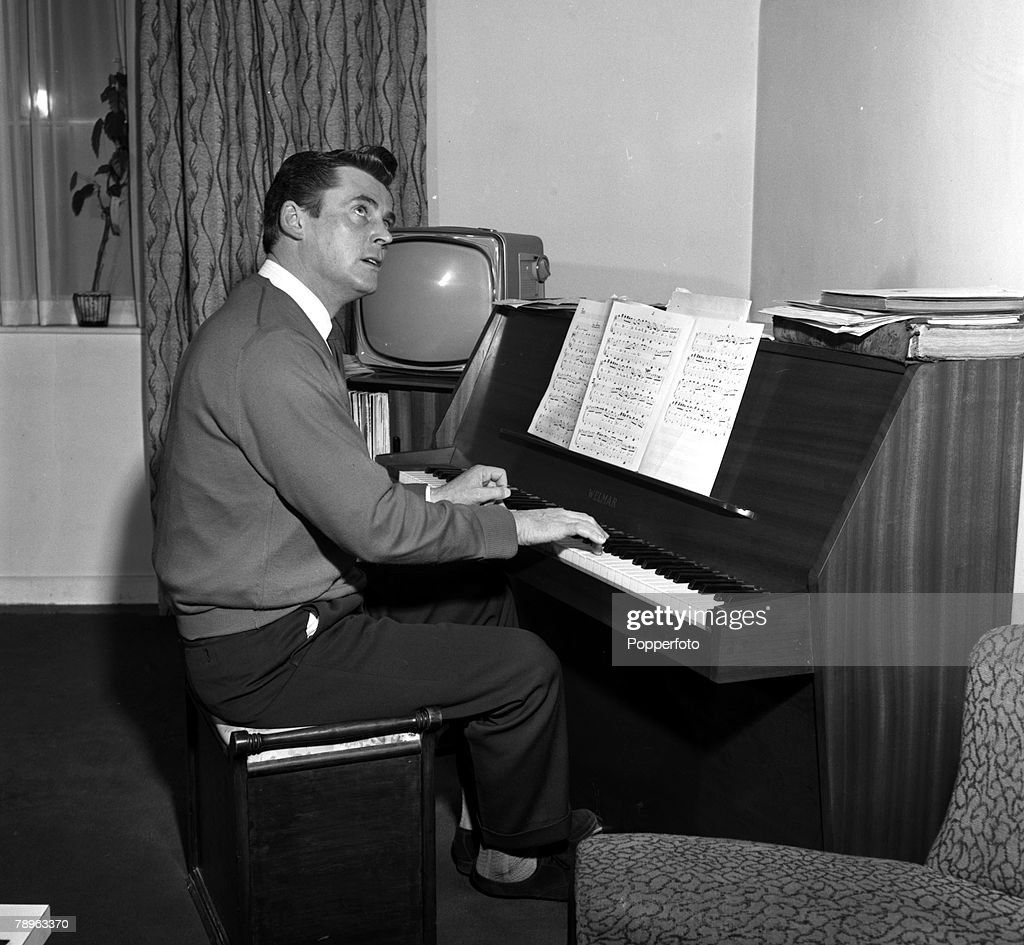 England, 1960, Pianist Russ Conway is pictured playing the piano at his home