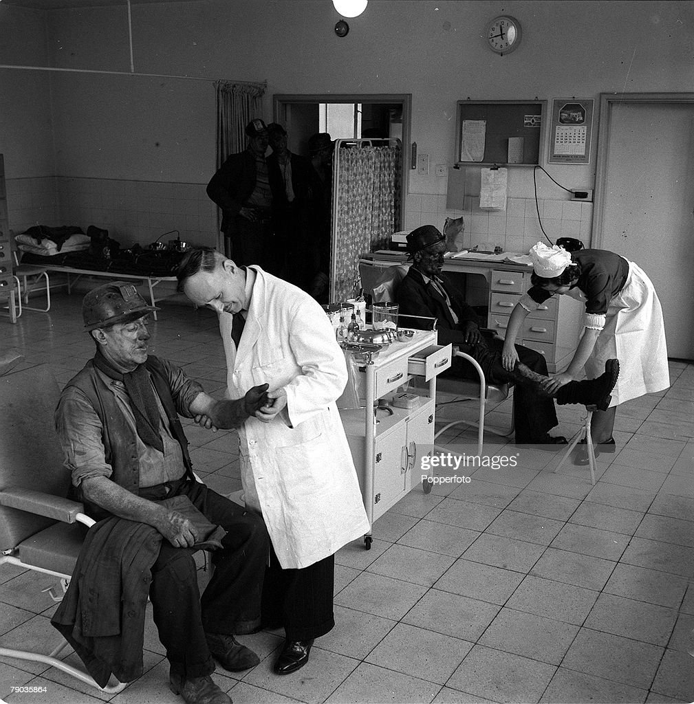 England, 1954, Pit Nurses, Two miners receive medical assistance from a doctor and nurse at a colliery surgery
