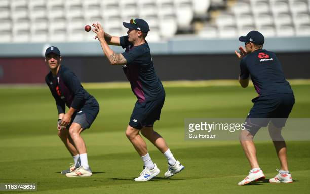 England player Jason Roy takes a catch as Rory Burns and Joe Root look on during England nets ahead of the Test Match against Ireland at Lord's...