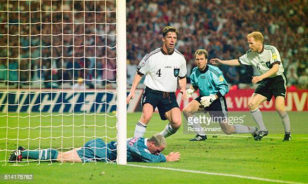 England player Paul Gascoigne reacts after failing to convert a cross as Germany players Steffen Freund Andreas Köpke and Matthias Sammer look on...