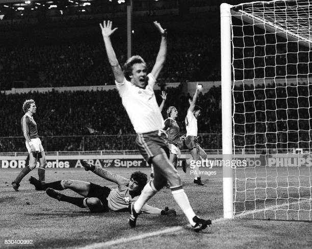 England player Phil Neal raises his arms in celebration as Switzerland's Markus Tanner puts the ball past his own goalkeeper to score an own goal...