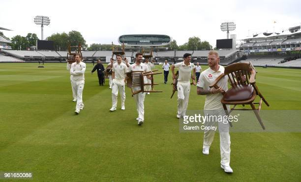 England players carry their chairs back to the pavilion after their team picture at Lord's Cricket Ground on May 23 2018 in London England
