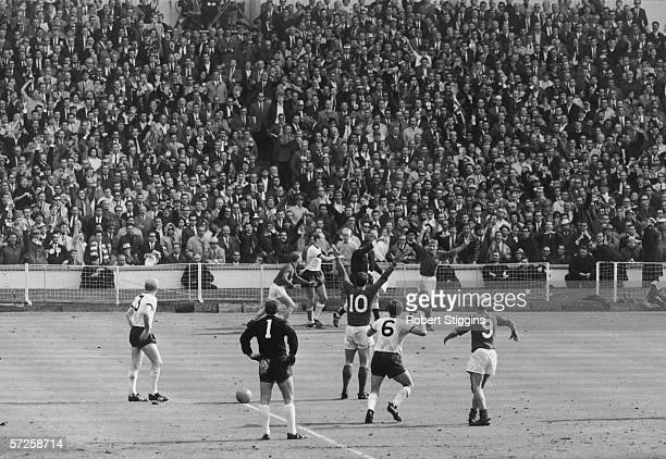 England players celebrate as referee Gottfried Dienst gives the controversial Geoff Hurst goal after consulting the linesman during the 1966 World...
