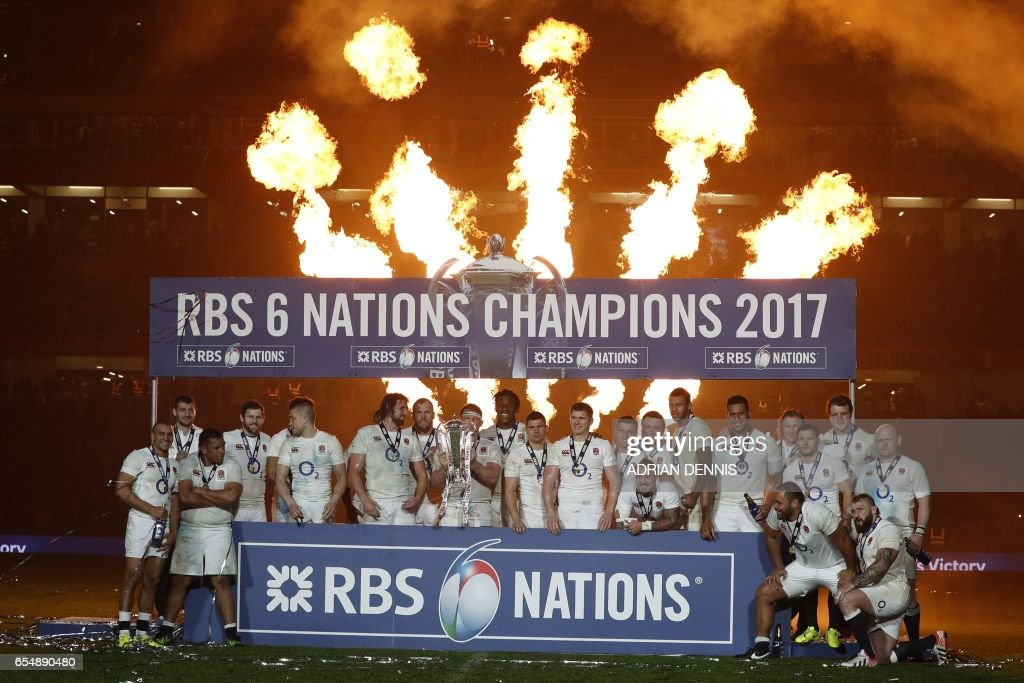 TOPSHOT - England players celebrate with the trophy after winning the Six Nations Championship on the pitch after the Six Nations international rugby union match between Ireland and England at the Aviva Stadium in Dublin on March 18, 2017. Ireland beat England 13-9 to deny the visitors a record-breaking Grand Slam victory in Dublin on Saturday. Had England, who'd already won a second straight Six Nations title, come out on top they would have surpassed the record of 18 consecutive Test wins they share with world champions New Zealand and become the first side in the Six Nations era to complete back-to-back Grand Slams. / AFP PHOTO / Adrian DENNIS