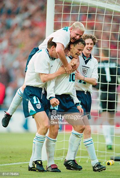 England players Darren Anderton Paul Gascoigne and Steve McManaman celebrate with goalscorer Teddy Sheringham after he had scored the second goal...