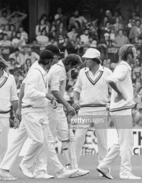 England players gather around Rick McCosker of Australia after getting hit in the face during the Centenary Test between Australia and England at the...
