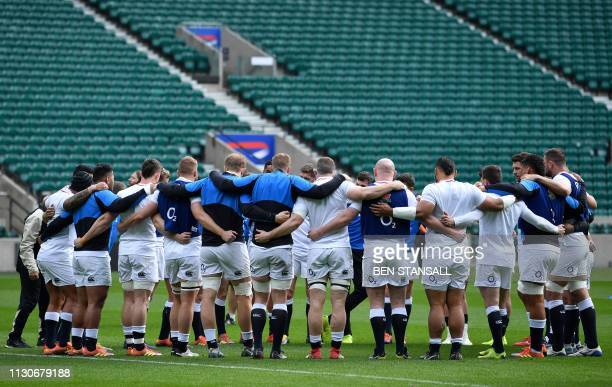 England players huddle during the captain's run training session at Twickenham stadium in south west London on March 15 on the eve of their Six...
