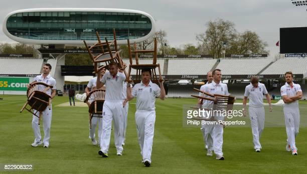 England players James Anderson Alastair Cook Stuart Broad Steven Finn Ian Bell Jonathan Trott Graeme Swann Joe Root and Nick Compton carry chairs and...